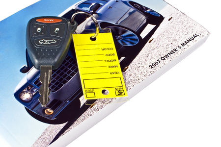 The key and owners maunal to your new car.  Isolated on white.  The key is still on the dealers key ring with a bright yellow tag. Stock Photo