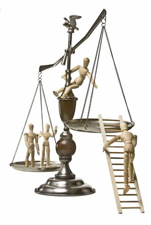 justice scales: Conceptual image for the struggle for equal rights.  Scales of justice with wooden mannequins climbing onto and accross the scales.  Two mannequins on the far side, one climbing a ladder onto the near side, and one perched on the scale itself to help him  Stock Photo