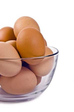 One dozen farm fresh brown eggs in a clear class bowl.  Isolated on white. Stock Photo
