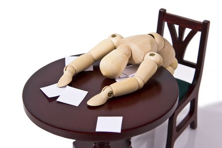 passed out: Exhausted wooden mannequin passed out over his desk.  Paperwork is strewn about.