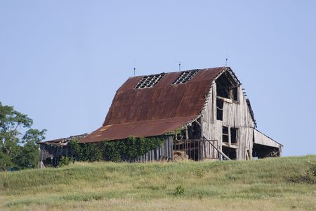 tin: Old barn sitting on a hill.  Weathered red tin roof.  Clear blue sky perfect for adding text.