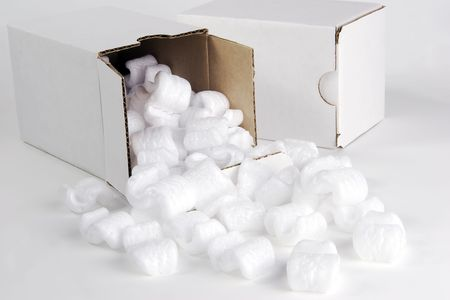 Two small white cardboard packing boxes.  White styrofoam packing peanuts are spilling from the open box.   photo
