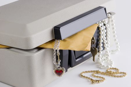 Small personal safe for protecting personal documents, jewels, etc. against fire damage.  Box is open with jewelery hanging out. Stock Photo