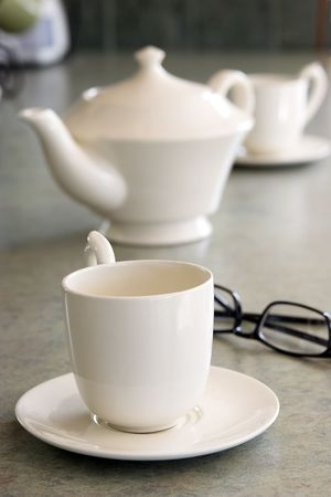 kitchen counter: White teapot and two cups on green marbled kitchen counter.