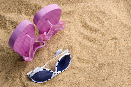 Pair of childs polka dotted sunglasses and pink flipflops in the sand at the beach.  The shoes are standing on end in the sand and the glasses lie in front.