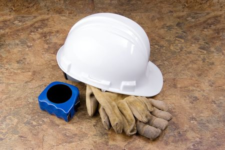 'tape measure': A white hard hat with well used work gloves and blue tape measure on a mottled background.