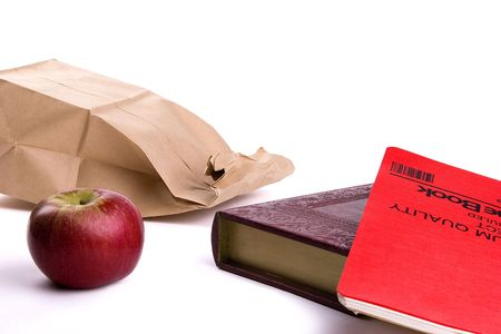 apple sack: Paper sack lunch with red apple, book, and red note pad on a white background.