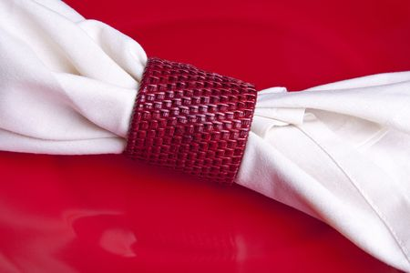 napkin ring: White cloth napkin in a red basket weave napkin ring laying on a red dinner plate.