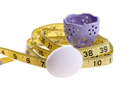 eggcup: An egg and purple eggcup with a yellow tape measure.  Conceptual image for dieting, weight loss, etc.