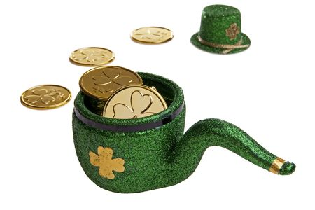Green Leprechauns pipe filled with lucky shamrock coins and a green top hat in the background. photo