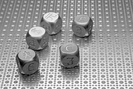 symbols: Metal dice with the currency symbols of Europe, England, United States, Russia, Japan, and China on a steel mesh background.