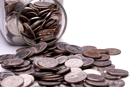 money jar: US coins spilling from a money jar. Stock Photo