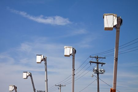 Row of five parked cherry picker bucket trucks against a blue sky. photo