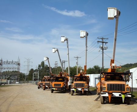 substation: Five utility bucket trucks parked beside an electrical substation. Stock Photo