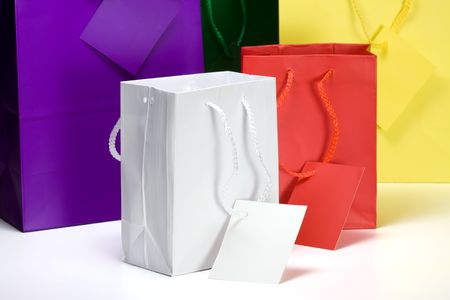 gift bags: Five colorful gift bags.  With rope handles and gift tags.  All empty and on a white background. Stock Photo