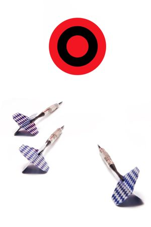 goal oriented: Three blue and white finned darts aimed at a red and black bulls-eye target.  A conceptual business image for  something to aim for, goal oriented, eye on the prize, etc.