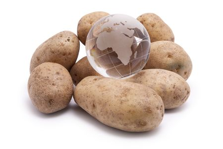 A pile of raw potatoes with a world globe on top.  Conceptual image for world hunger, feeding the world, etc. photo