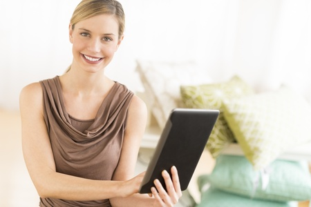Portrait of happy female owner with digital tablet in bedding store photo