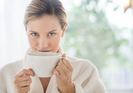 Close-up portrait of beautiful young woman drinking coffee in health spa Standard-Bild