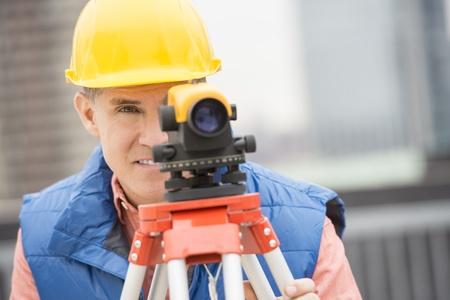 surveyor: Trabajador de construcción maduro medir distancias con el teodolito en el sitio de construcción