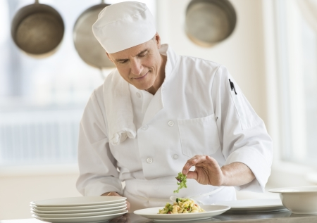 chefs whites: Front view of mature male chef garnishing dish at counter in commercial kitchen