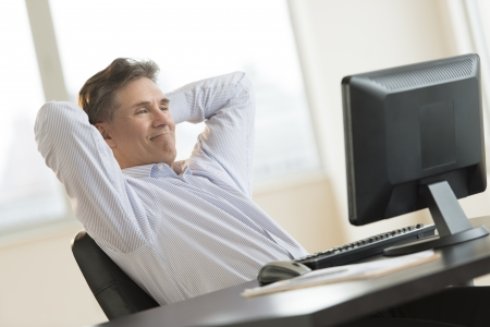 Mature businessman with hands behind head relaxing while looking at Desktop PC in office photo