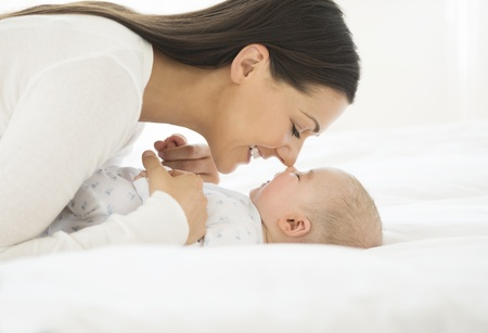Side view of a young woman playing with her little baby in bed photo
