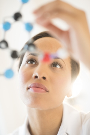 scrutinize: Low angle view of young female researcher analyzing molecular structure in laboratory