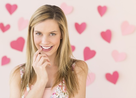 shy woman: Portrait of shy young woman with heart shaped papers stuck against pink background