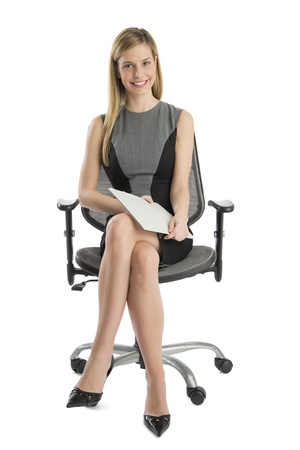 Full length portrait of beautiful businesswoman with file sitting on office chair against white background photo