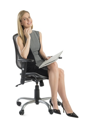 Full length portrait of happy businesswoman with file sitting on office chair against white background photo