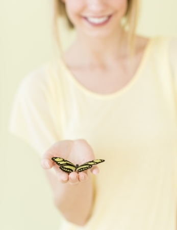 donna farfalla: Sezione centrale close-up della giovane donna farfalla nel palmo della mano contro sfondo colorato