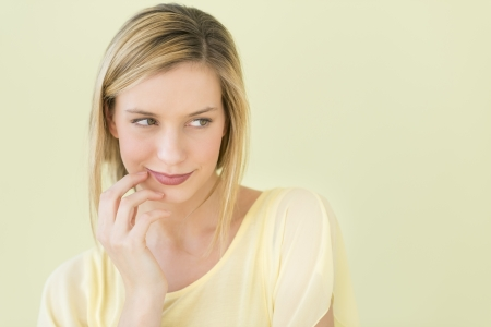 shy woman: Thoughtful young woman looking away against green background Stock Photo