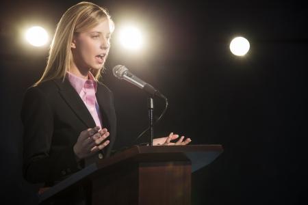 Young businesswoman giving speech at podium in auditorium
