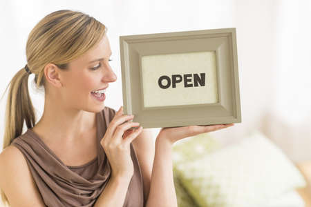 Happy young female owner holding open sign in bedding store photo