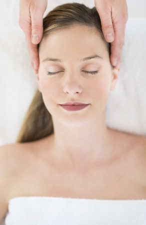 Directly above shot of beautiful young woman receiving head massage at health spa