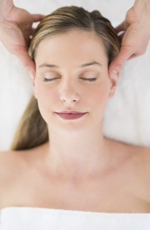 Directly above shot of relaxed young woman receiving head massage at health spa photo