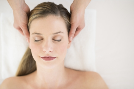 Directly above shot of attractive young woman receiving head massage at health spa photo