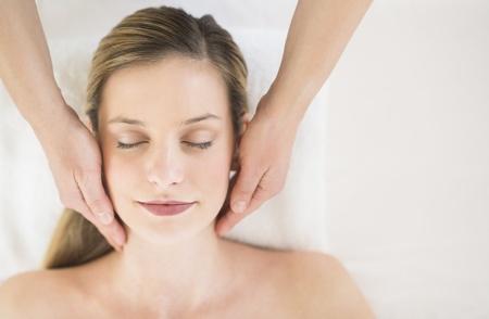 mimos: Justo encima de tiro de una mujer joven relajada recibiendo masaje de cabeza en el balneario de la salud