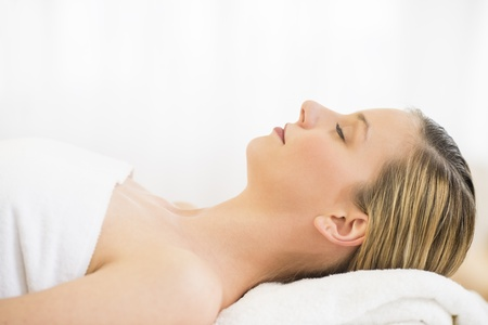 massage table: Side view close-up of beautiful young woman resting on massage table in health spa