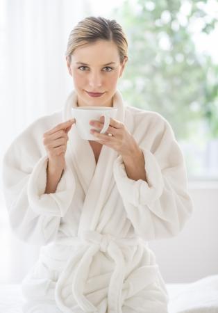 mimos: Retrato de mujer joven y hermosa con la taza de café, sentado en la mesa de masaje en el spa Foto de archivo