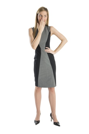 sideways glance: Full length of young businesswoman looking away while covering mouth with hand isolated against white background
