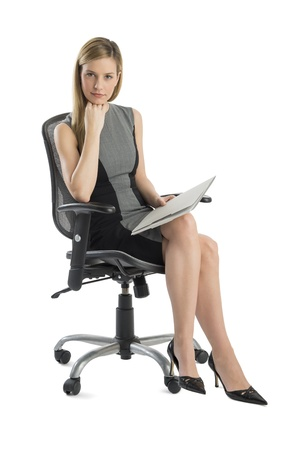 Full length portrait of confident businesswoman with file sitting on office chair isolated over white background
