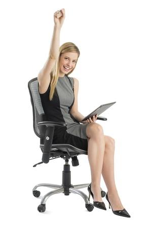 Full length portrait of happy businesswoman with digital tablet celebrating success while sitting on chair against white background Standard-Bild