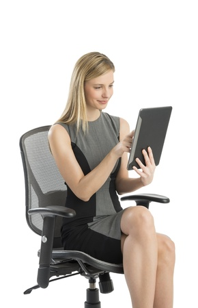 Beautiful young businesswoman using digital tablet while sitting on office chair against white background photo