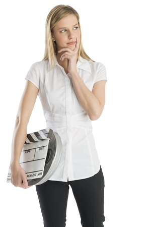 three people only: Thoughtful young woman with hand on chin holding film slate and reel while looking away against white background