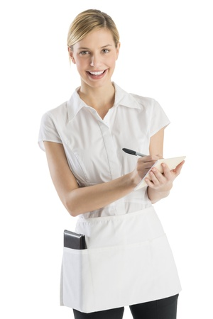 Portrait of happy young waitress with order pad and pen standing against white background