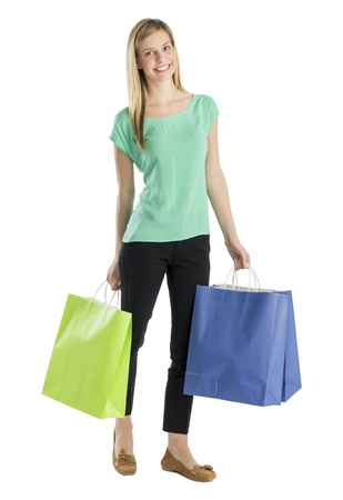 Full length portrait of happy young woman with shopping bags standing against white background photo