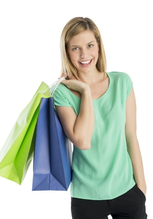 Portrait of happy young woman with hand in pocket carrying shopping bags against white background photo