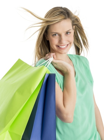 Portrait of beautiful young woman carrying shopping bags isolated over white background photo